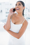 Laughing toned brunette phoning with mobile phone