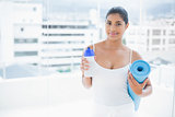Content toned brunette holding sports bottle and exercise mat