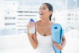 Laughing toned brunette holding sports bottle and exercise mat