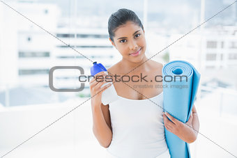 Pleased toned brunette holding sports bottle and exercise mat