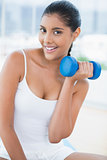 Cheerful toned brunette sitting on floor with dumbbells