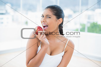 Excited toned brunette holding apple