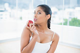 Calm toned brunette holding apple