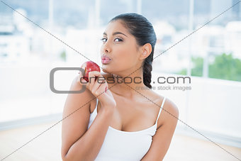 Calm toned brunette holding apple