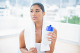 Serious toned brunette with towel holding sports bottle