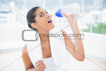 Calm toned brunette with towel holding sports bottle