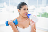 Happy toned brunette holding dumbbells and sports bottle