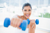 Cheerful toned brunette boxing dumbbells towards camera