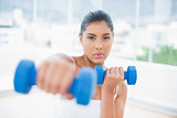 Serious toned brunette boxing dumbbells towards camera