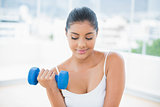Peaceful toned brunette holding dumbbells