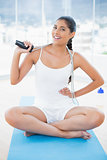 Smiling toned brunette sitting on floor with skipping rope