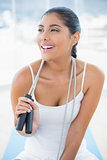 Laughing toned brunette sitting on floor with skipping rope