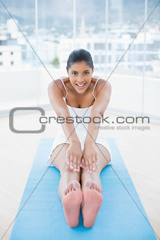 Happy toned brunette sitting on floor stretching legs