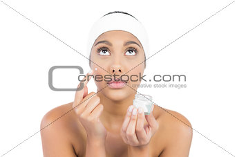 Calm nude brunette using moisturizer looking up