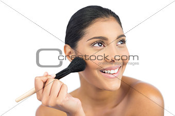 Smiling nude brunette using powder brush