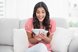 Excited cute brunette sitting on couch holding money