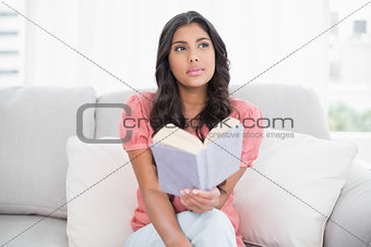 Thoughtful cute brunette sitting on couch reading a book