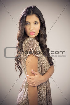 Sexy beautiful brunette looking at camera touching arm