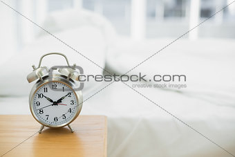 Retro alarm clock standing on a bedside table