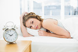 Beautiful tired woman looking at camera lying in her bed
