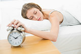 Exhausted young woman turning off the alarm clock