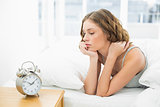Young woman lying in her bed looking at the alarm clock