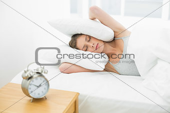 Beautiful woman holding her ears closed by using pillow while lying in her bed