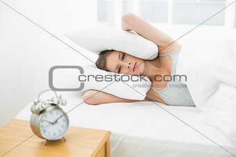 Annoyed young woman holding her ears closed by using pillows while lying in her bed