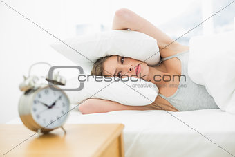 Tired young woman lying in her bed covering her ears with pillow