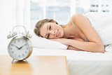 Beautiful calm woman lying in her bed under the cover