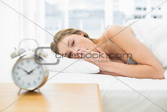 Attractive tired woman lying in her bed under the cover