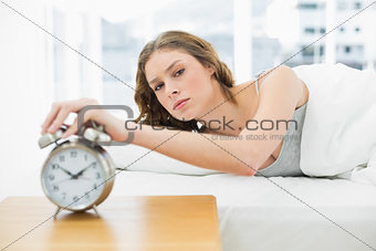 Annoyed beautiful woman turning off the alarm clock while lying in her bed