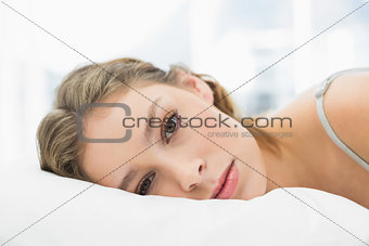 Portrait of tired pretty woman lying in her bed in the bedroom
