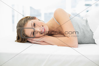 Smiling calm woman resting in her bed