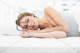 Beautiful tired woman lying in her bed under the cover