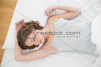 Calm woman sleeping lying under the cover on her bed