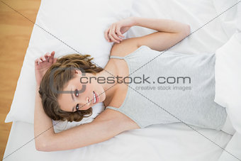 Attractive slender woman lying under the cover on her bed