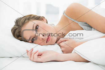Calm woman lying under the cover on her white bed