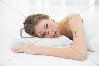 Beautiful relaxed woman lying on her bed under the cover