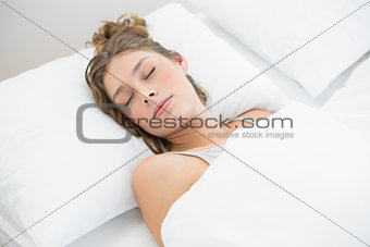 Calm young woman sleeping lying under the cover on her bed