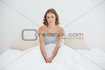 Attractive slim woman sitting on her bed in the bedroom