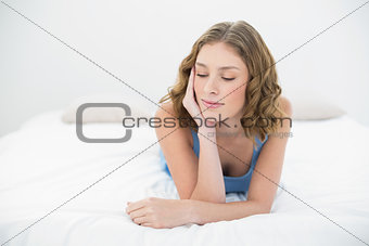Attractive calm woman lying on her bed in the bedroom