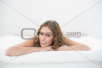 Beautiful young woman lying on her bed on her belly