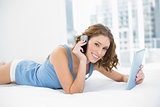 Portrait of pretty young woman holding her tablet while phoning and lying on her bed