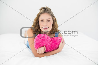 Attractive sweet woman cuddling with her heart pillow smiling at camera