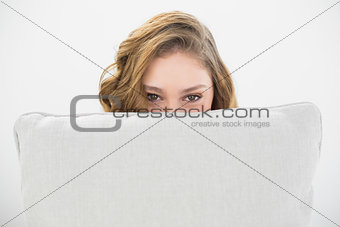 Beautiful brunette woman hiding her face behind a white pillow
