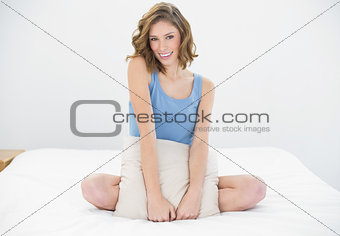 Attractive woman sitting on her bed holding a white pillow