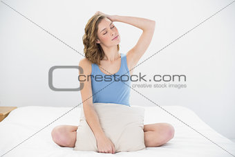 Attractive woman posing sitting on her bed holding a pillow
