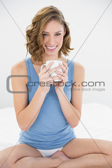Calm woman sitting on her bed holding a white cup
