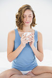 Content peaceful woman sitting on her bed holding white cup